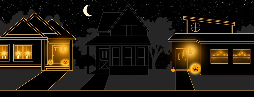 Three houses sit in a row on a street at night. The middle house is dark but each house on other side is lit up with Halloween decorations.