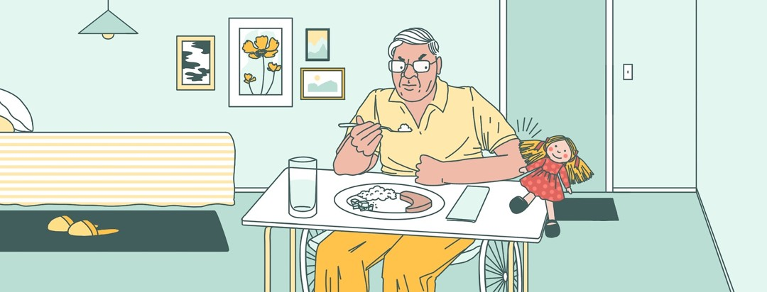 An elderly man sit in a wheelchair with a meal try. He angrily looks at a rag doll on the tray that he is bumping off on to the floor with his elbow.