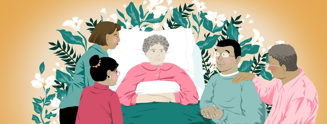 A family gathers around an elderly and ill woman with alzheimers in a hospital bed. Behind her bed is a large number of flowers.