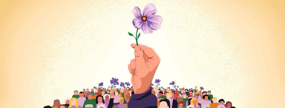 A single purple flower is held up by a hand. In the background, a crowd of all kinds of different people of different ages holds up purple flowers.