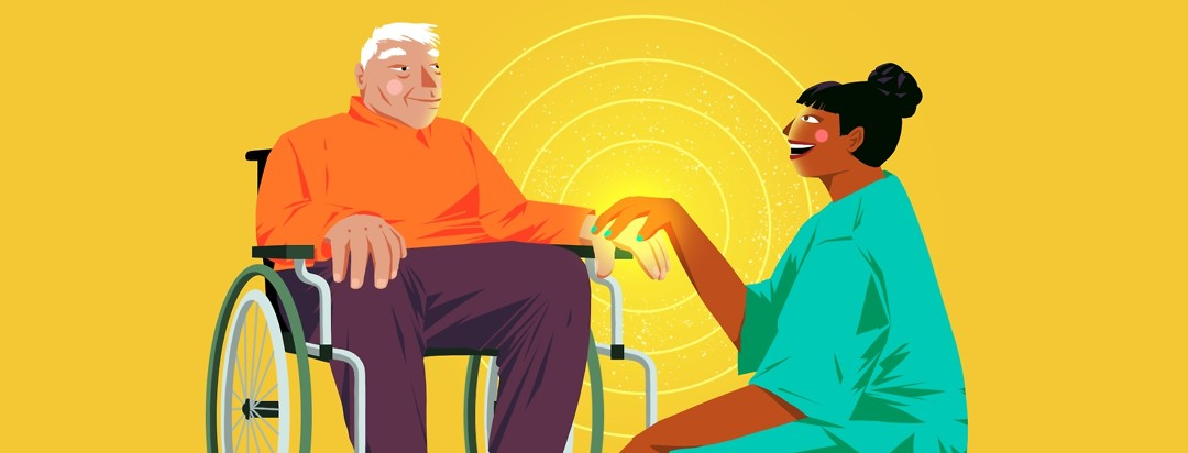 An elderly man in a wheelchair smiles at a nurse who is crouching down next to him with her hand on his.