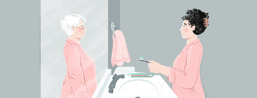 A younger woman in pajamas stands in front of a mirror holding a toothbrush with toothpaste on it. The reflection in the mirror shows an older version of herself.