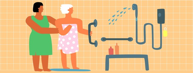 An older woman in a towel is helped into a shower with many assistive devices like bars and handles and a bench by a younger woman wearing a dress.