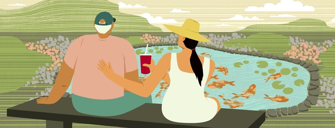 An older man and younger woman sit together on a bench facing a koi pond and serene landscape. The woman has her hand on the man's back and offers him a milkshake.