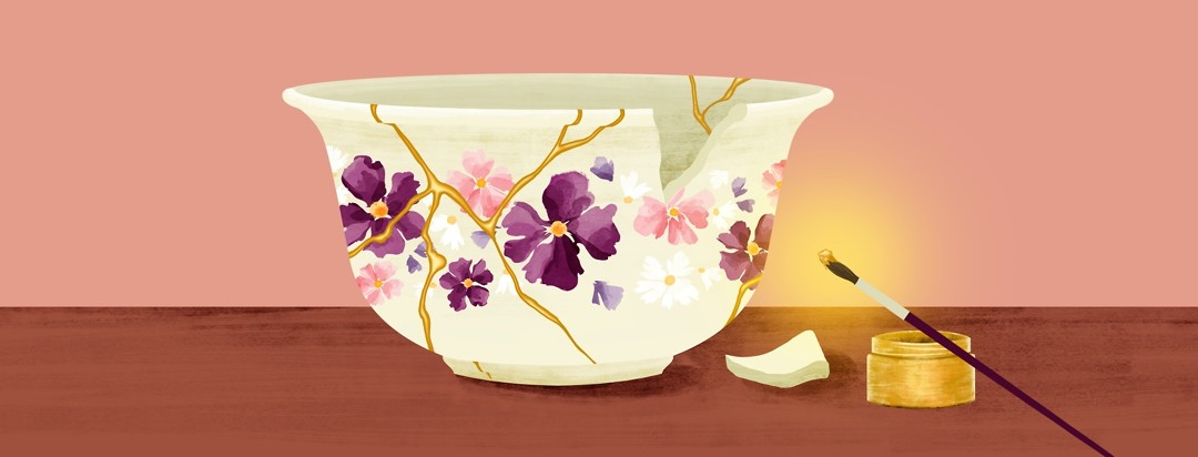 A chipped ceramic bowl with a floral pattern is being repaired with gold.