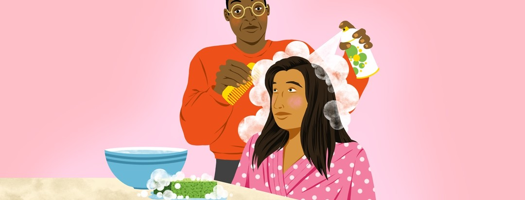 A man sprays dry shampoo and combs it into a woman's hair. The woman is wearing a robe and is seated in front of a table that also features a bowl of water and a soapy sponge.