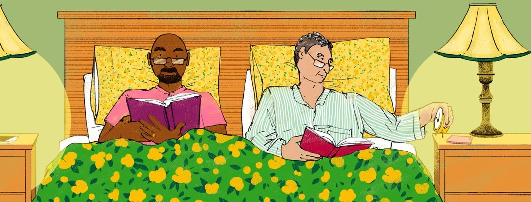 Two men read in bed. One is checking the time on an analog clock.
