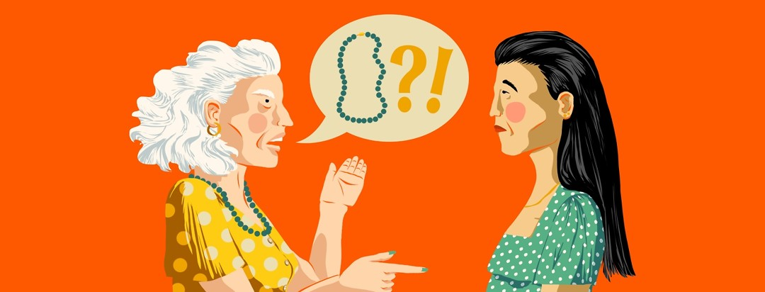 An angry, older woman yells at a younger woman about a necklace that she can't find (but is actually hanging around her neck).