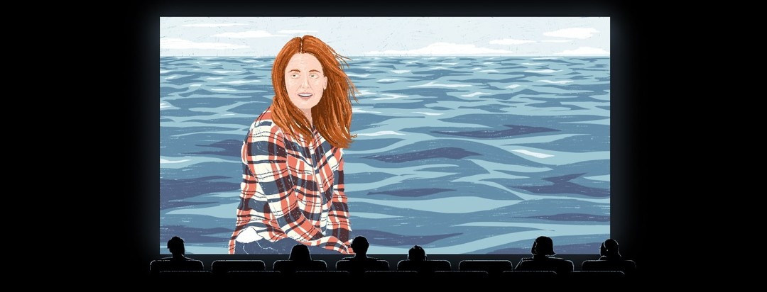A still image from the movie Still Alice on a movie screen shows Julianne Moore sitting against a, ocean background. The silhouettes of people in the theater seats are slightly illuminated by the screen.