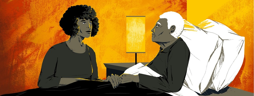 A younger woman sits at eye level and speaks gently to an elderly person in bed. A lamp emitting warm light is lit behind them.