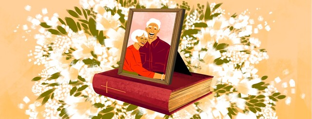 A framed photo of an older couple rests on a worn Bible. The background shows a large display of white flowers.