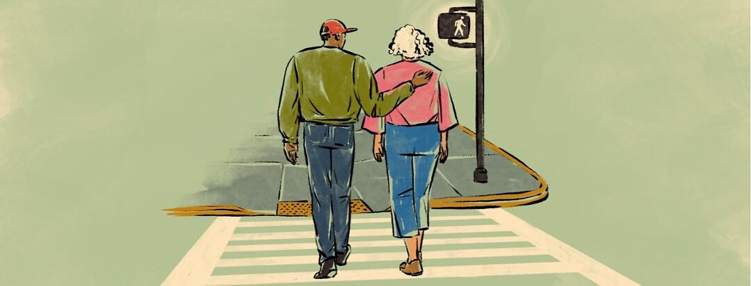 alt=A younger man guides an older woman across a street.