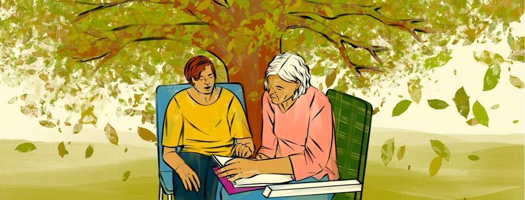 A younger woman and an older woman go over paperwork together under a tree.