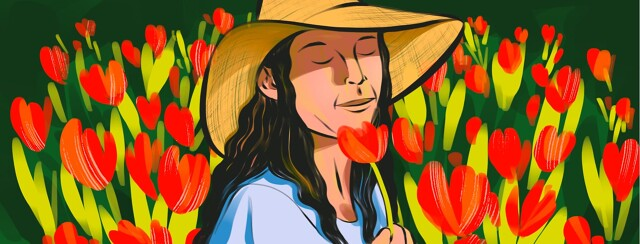 alt=A woman in a sunhat closes her eyes and smells a flower she is holding, while standing in a field of red flowers