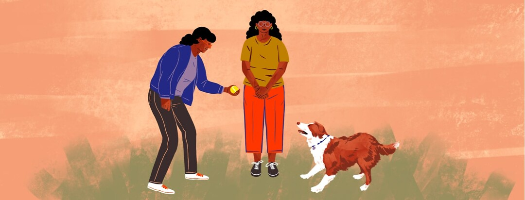alt=an elderly woman holds a ball for dog while a younger woman looks on.
