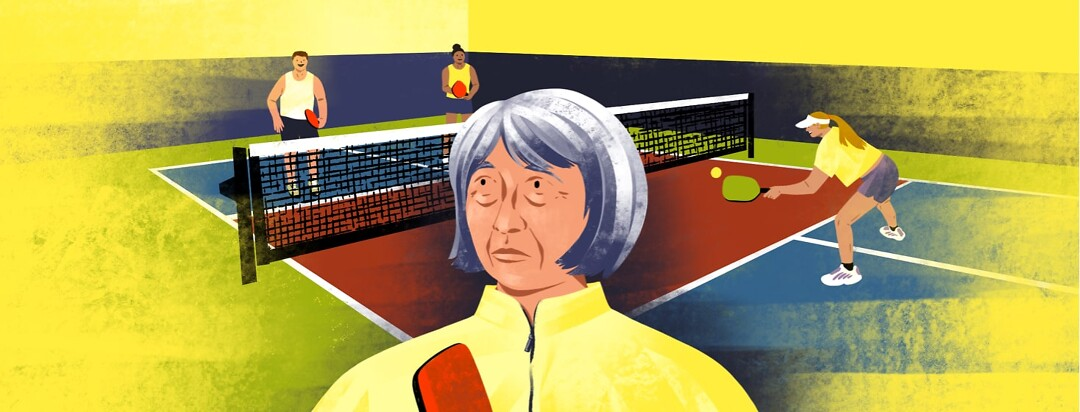alt=An older woman looks confused. Behind her are people playing on a pickleball court.